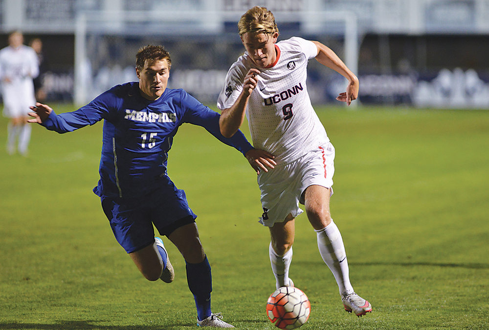 UConn men's soccer forward Fredrik Jonsson fights off a Memphis defender during the Huskies' game against the TIgers at Joseph J. Morrone Stadium in Storrs, Connecticut on Saturday, Oct. 3, 2015. (Amar Batra/The Daily Campus)