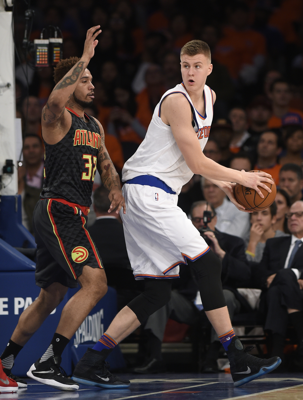 New York Knicks forward Kristaps Porzingis (6) looks to pass the ball around Atlanta Hawks forward Mike Scott (32) during the second half of an NBA basketball game on Thursday, Oct. 29, 2015, in New York. The Hawks won 112-101. (Kathy Kmonicek/AP)