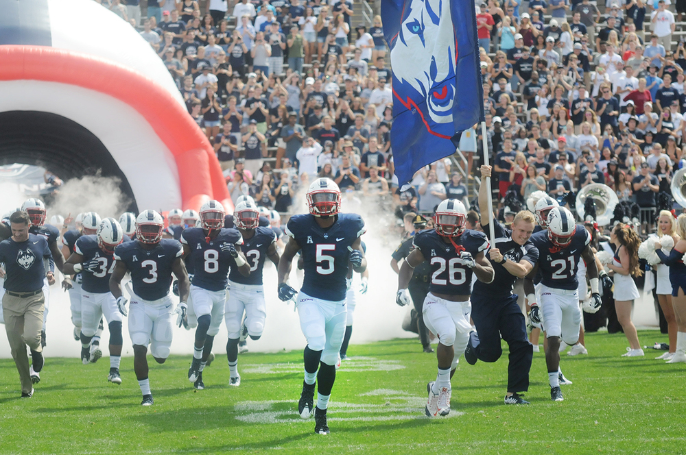 In this photo, members of the UConn football team run out of the tunnel at Pratt & Whitney Stadium at Rentschler Field prior to its game against Army on Saturday, Sept. 12, 2015. The team must win one of its final two games to become bowl eligible. (Bailey Wright/The Daily Campus)
