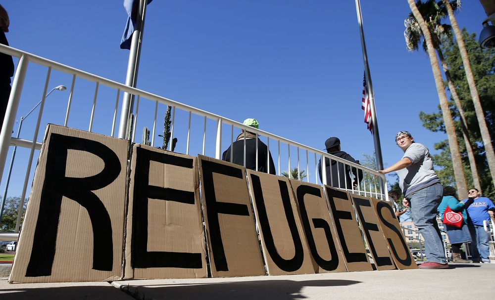 A sign welcoming Syrian refugees is placed at the entrance to the office of the Arizona governor during a rally at the Arizona Capitol Tuesday, Nov. 17, 2015, in Phoenix. Arizona Gov. Doug Ducey has joined a growing number of governors calling for an immediate halt to the placement of any new refugees in the wake of terrorist attacks in Paris. The U.S. State Department says Arizona has received 153 Syrian refugees so far this year. (Ross D. Franklin/AP)