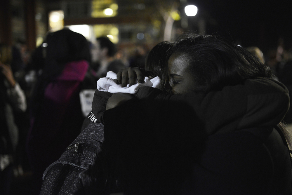 "Students embrace at a vigil held by Asian American Cultural Center (AsAAC) as part of a series named ""Salaam,"" which means ""peace"" in Arabic. Angela Rola, Director of AsACC, said Salaam got its name for that reason. (Jason Jiang/Daily Campus)"