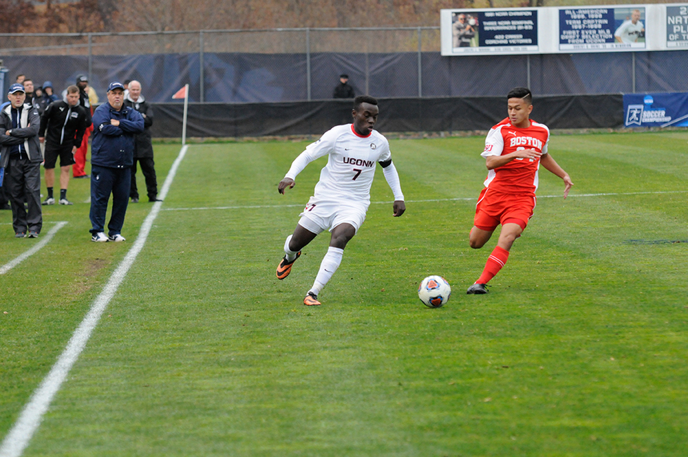 UConn men's soccer junior midfielder Kwame Awuah dribbes the ball during the Huskies' NCAA tournament game against Boston University at Morrone Stadium in Storrs, Connecticut on Thursday, Nov. 19, 2015. Awuah recorded two goals and an assist to lead UConn past the Terriers 3-1. (Amar Batra/The Daily Campus)