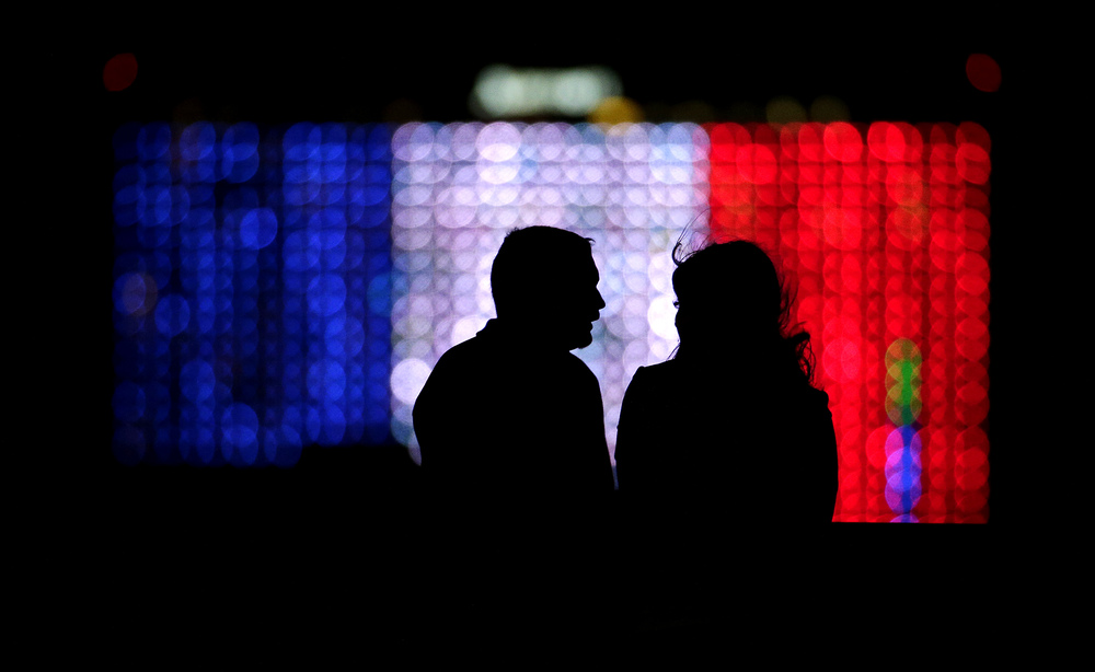 A couple is silhouetted against a hotel lit with the colors of the French flag to show solidarity with the victims of last week's attacks in Paris as they look over downtown Kansas City, Mo., Tuesday, Nov. 17, 2015. (Charlie Riedel/AP)