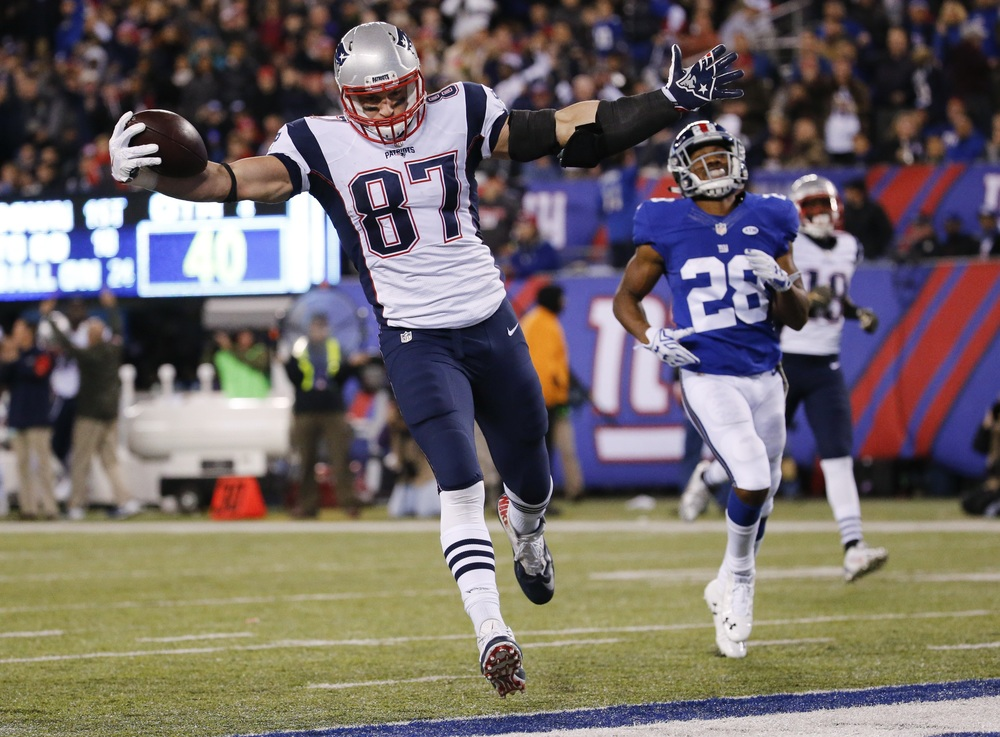 In this Nov. 15, 2015, file photo, New England Patriots' Rob Gronkowski (87) scores a touchdown in front of New York Giants' Jayron Hosley (28) during the second half of an NFL football game in East Rutherford, N.J. (Julio Cortez/AP)