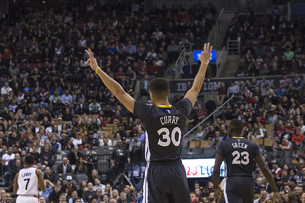 Golden State Warriors' Stephen Curry celebrates after teammate Jason Thompson scores a three point shot against the Toronto Raptors during the first half of an NBA basketball game in Toronto, Saturday, Dec. 5, 2015. (Chris Young/The Canadian Press via AP)