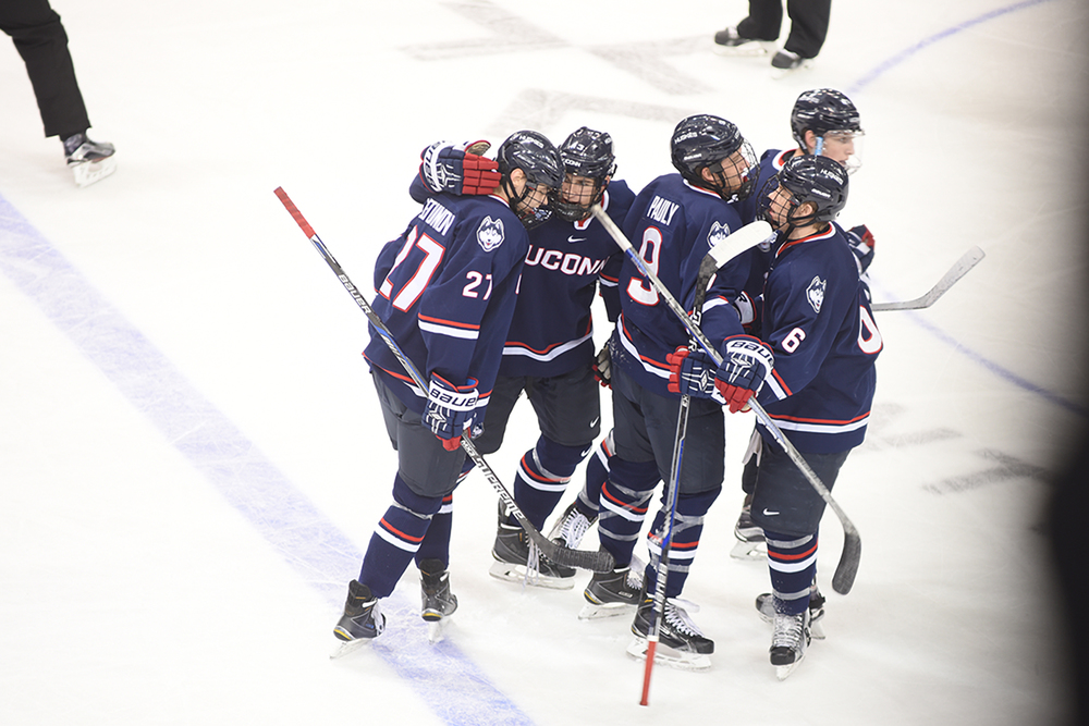 A pack of Huskies celebrate during UConn's 4-3 victory over No. 5 UMass-Lowell. UConn swept both games of a home-and-home series this weekend. (Zhelun Lang/The Daily Campus).