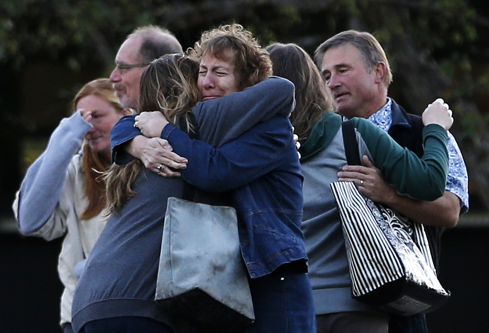 "Faculty members embrace as they are allowed to return to Umpqua Community College Monday, Oct. 5, 2015, in Roseburg, Ore. The Connecticut Board of Regents for Higher Education moved closer Thursday toward allowing armed security on all state community college campuses, with proponents acknowledging ""the world is a different place."" (AP)"