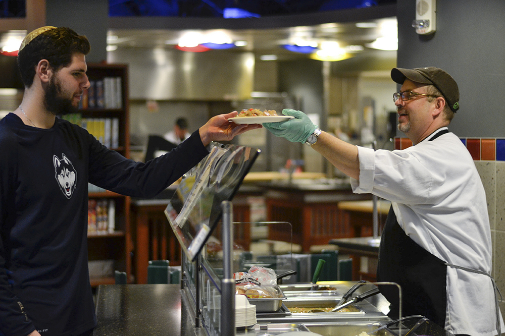 "Marty Grimson (right) serves first-semester student David Ellner. The staff at Kosher keep up to date with the lives and schedules of their regular customers. The bond between the staff and students is unlike any other dining facility on campus. Grimson said he attributes this to the fact that the staff at Kosher view the kitchen as an extension of themselves. ""When you come the dining hall and you eat at Kosher, you are a guest of mine,"" Grimson said. (Rebecca Newman/The Daily Campus)"