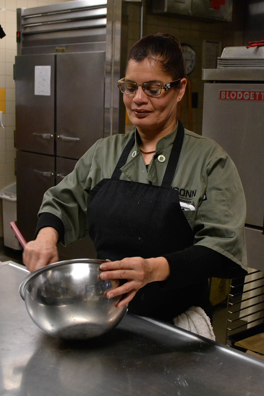 "Ivette Pagan, a kitchen assistant at the Nosh Kosher Kitchen, mixes frosting for a desert. ""The cooks are always so welcoming and ready to feed me; I feel like I'm in my home here."" – Nathan Schachter, first semester communications and theater double major who regularly eats at Kosher. (Rebecca Newman/The Daily Campus)"