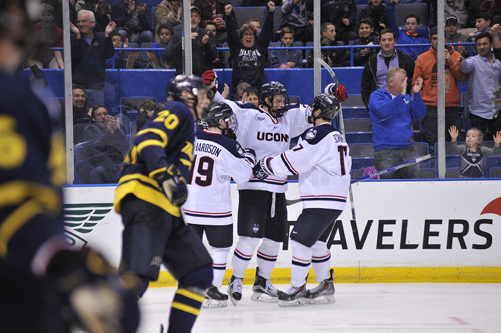 UConn men's ice hockey forward Jeff Wight (middle) celebrates with teammates Evan Richardson (left) and Jesse Schwartz (right) after scoring a goal during the Huskies' game against Merrimack at XL Center in Hartford, Connecticut on Friday, Dec. 11, 2015. (Jason Jiang/The Daily Campus)