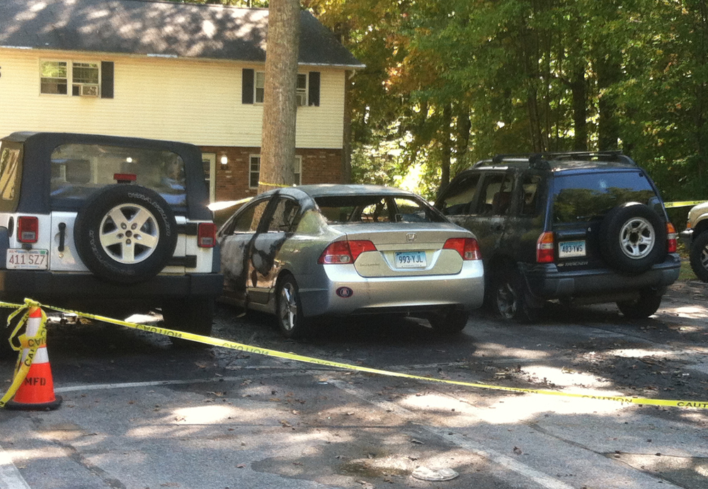 In this photo, three cars that were on fire in front of a Carriage House apartment are pictured on Oct. 11, 2015. The silver Honda (middle) was originally set on fire, and the fire spread to the cars on the left and right. (Courtesy)