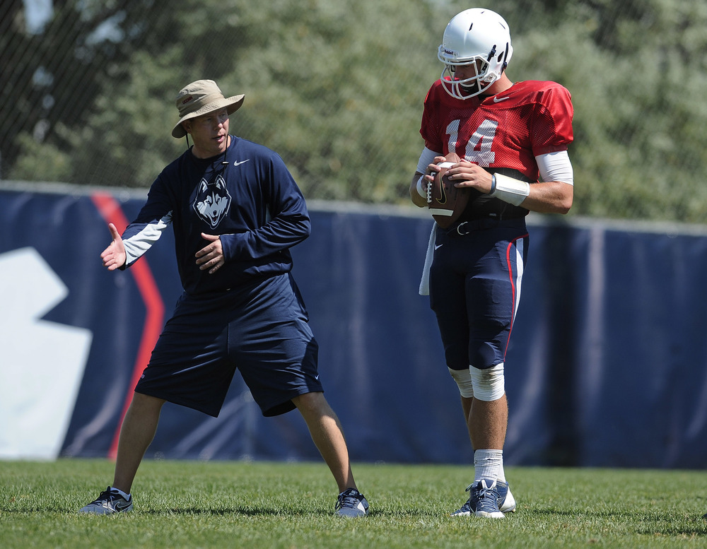 UConn quarterback coach Wayne Lineburg talks with quarterback Tim Boyle during a practice on Wednesday, Aug. 12, 2015, in Storrs, Conn. (Jessica Hill/AP)
