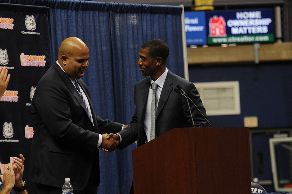 Warde Manuel (left) greets Kevin Ollie (right) at a press conference. It was reported today that Manuel will be leaving UConn to accept the athletic director position at the University of Michigan. (FILE Photo)