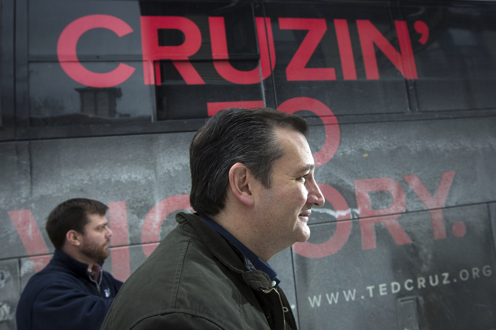 In this Jan. 19, 2016, photo, Republican presidential candidate, Sen. Ted Cruz, R-Texas passes his campaign bus as he arrives for a campaign stop at the Freedom Country Store in Freedom, N.H. Cruz is dreaming of a face-off with Democratic front-runner Hillary Clinton, even before the first primary votes are cast. He warns his supporters about what he thinks America will look like under a Clinton administration, predicting a nuclear-armed Iran, amnesty for millions of people in America illegally and the continuation of President Barack Obama's health care law. (AP)
