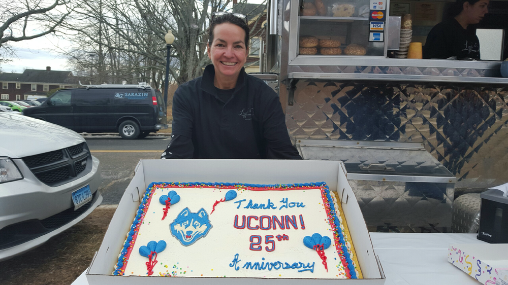 "Lizzie Searing of Lizzie's Catering and Lizzie's Curbside, the well-known food truck often parked outside of the Arjona Building, holding her ""thank you"" cake marking her 25 years on campus. Cake and coffee was free this morning as part of the celebration. (Annabelle Orlando/Daily Campus)"