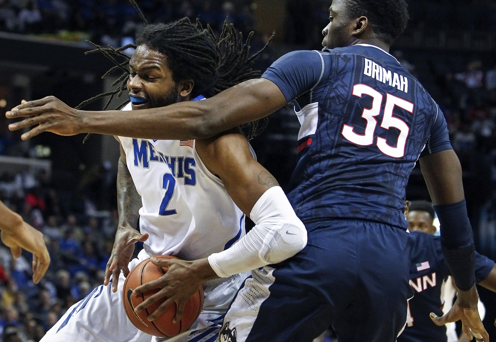 University of Memphis forward Shaq Goodwin, left, takes a shot to the face while driving around Connecticut University center Amida Brimah during first half action at the FedExForum Thursday, Feb. 4, 2016. (Mark Weber/The Commercial Appeal via AP)