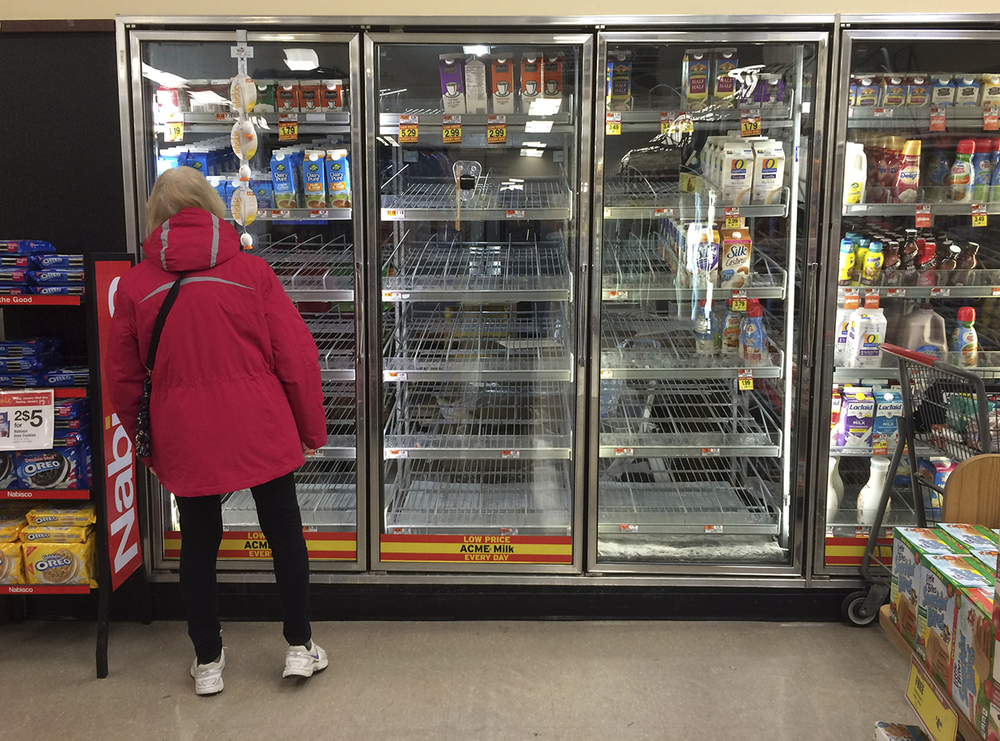 A woman peers into an empty dairy refrigerator at a grocery store, Friday, Jan. 22, 2016, in Philadelphia. (AP Photo/Matt Slocum)