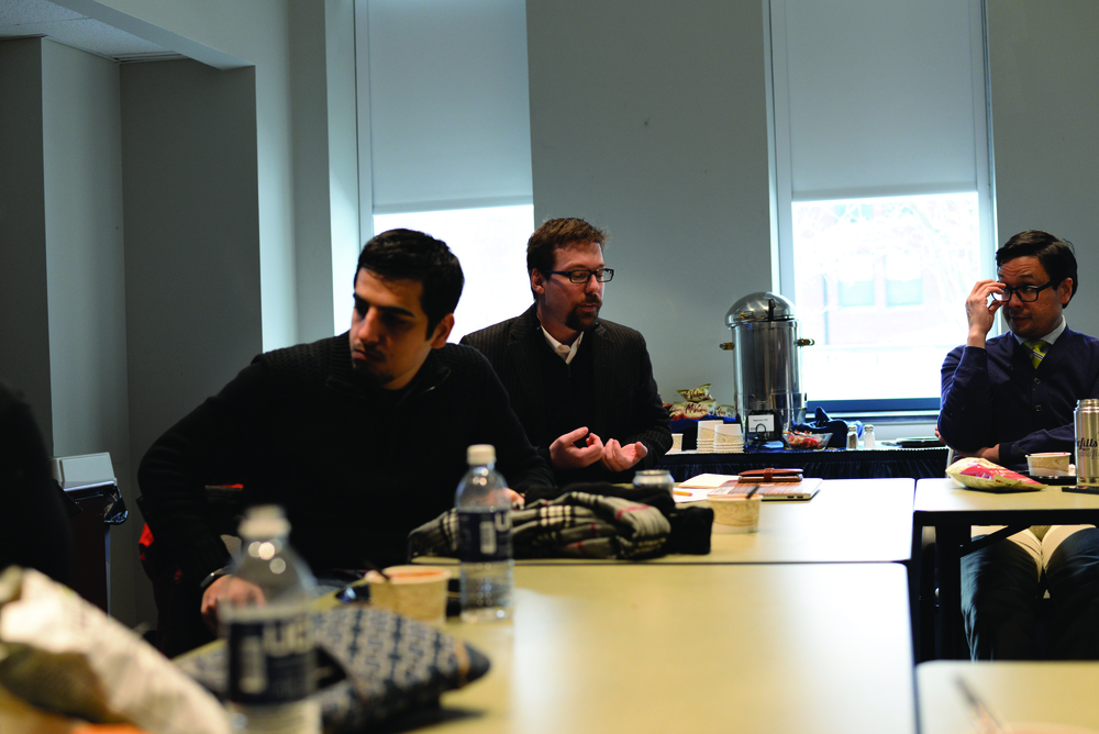 Human Rights Institute postdoctoral fellow Andrew Janko (middle) speaks to colleagues at his refugee research presentation. (Amar Batra/Daily Campus)