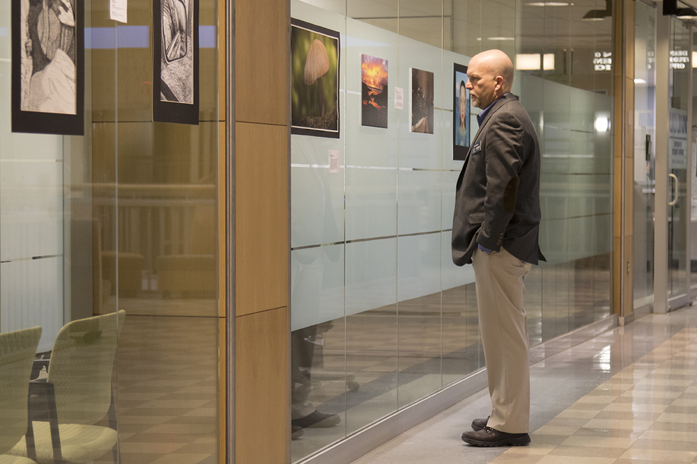 John Bau, a career consultant in UConn's School of Engineering, views artwork during a student art exhibition hosted by the Center for Career Development on the second floor of the Wilbur Cross Building on Wednesday, Feb. 10, 2016. (Jackson Mitchell/The Daily Campus)