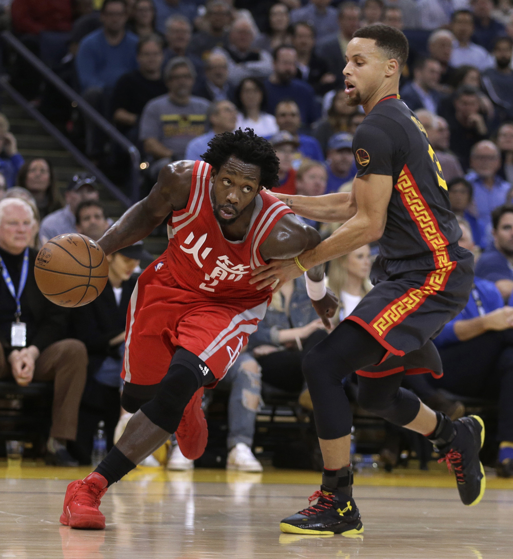 Houston Rockets' Patrick Beverley, left, drives the ball against Golden State Warriors' Stephen Curry during the first half of an NBA basketball game Tuesday, Feb. 9, 2016, in Oakland, Calif. Curry was the winner of the 2015 Three Point Contest and Beverly won the Skills Challenge. (AP Photo/Ben Margot)