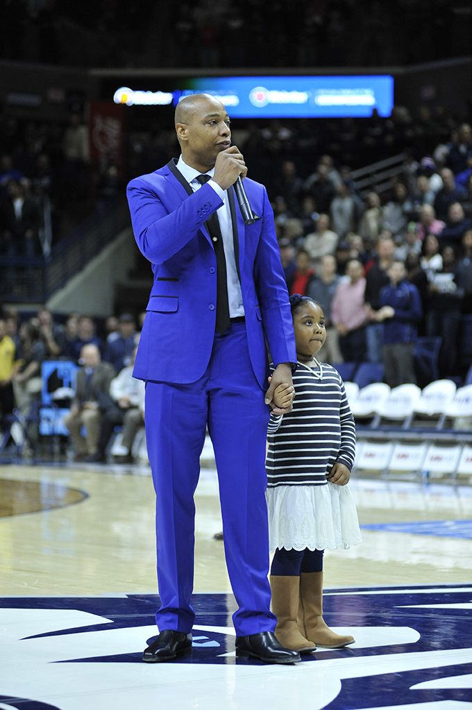 An emotional Caron Butler, holding his daughter's hand, addresses the crowd. (Jason Jiang/The Daily Campus)