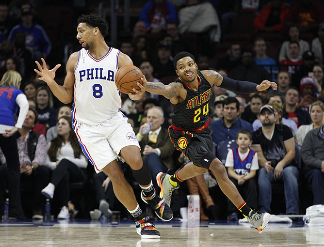 Atlanta Hawks' Kent Bazemore (24) tries to knock the ball away form Philadelphia 76ers' Jahlil Okafor (8) during the second half of an NBA basketball game, Wednesday, Feb. 3, 2016, in Philadelphia. The Hawks won 124-86. (AP Photo/Chris Szagola)