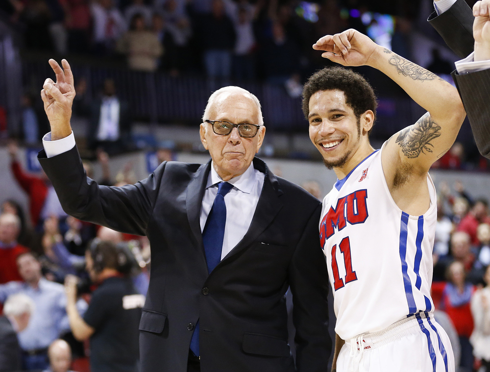 SMU coach Larry Brown and guard Nic Moore (11) celebrate during SMU's alma mater following the team's NCAA college basketball game against Gonzaga, Saturday, Feb. 13, 2016, in Dallas. SMU won 69-60. (AP Photo/Jim Cowsert)