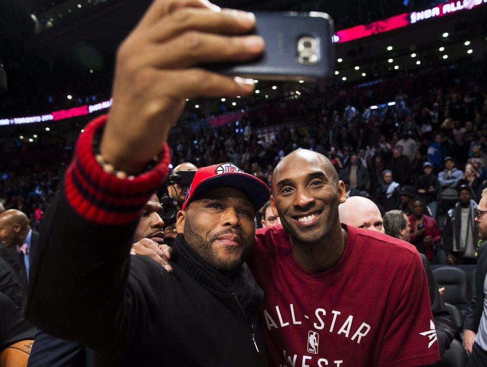 Western Conference's Kobe Bryant, of the Los Angeles Lakers, right, poses for a selfie with actor Anthony Anderson during second half NBA All-Star Game basketball action in Toronto on Sunday, Feb. 14, 2016. (Mark Blinch/The Canadian Press via AP)