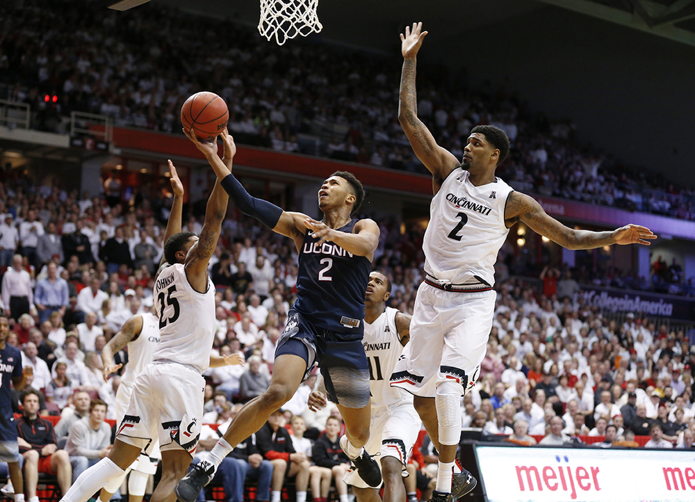 Connecticut guard Jalen Adams, center, shoots between Cincinnati's Kevin Johnson (25) and Octavius Ellis (2)during the second half of an NCAA college basketball game Saturday, Feb. 20, 2016, in Cincinnati. (AP Photo/Gary Landers)