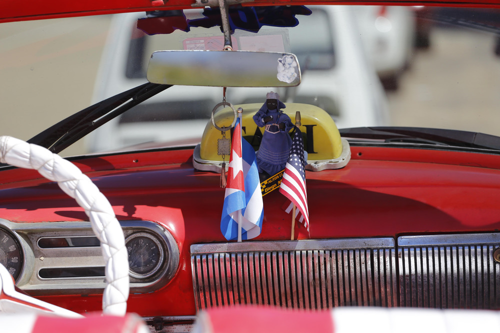The stars and stripes and the Cuban national flag are placed together on the dashboard of a vintage American convertible in Havana, Cuba, Thursday, Feb. 18, 2016. President Barack Obama said that he will visit Cuba on March 21-22, making him the first sitting president in more than half a century to visit the island nation. (AP Photo/Desmond Boylan)