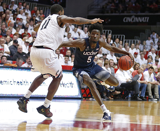 Connecticut guard Daniel Hamilton (5) drives the ball against Cincinnati forward Gary Clark (11) during the second half of an NCAA college basketball game Saturday, Feb. 20, 2016, in Cincinnati. (AP Photo/Gary Landers)