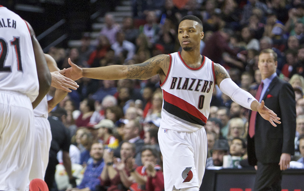 Portland Trail Blazers guard  Damian   Lillard  high-fives a teammate after scoring against the Golden State Warriors during the second half of an NBA basketball game in Portland, Ore., Friday, Feb. 19, 2016. Portland won 137-105. (AP Photo/Craig Mitchelldyer)
