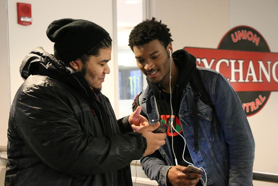 Sathia Diaz (left) shares what music he's listening to on his iPhone in the UConn Student Union on Thursday, Feb. 25, 2016. (Diler Haji/The Daily Campus)