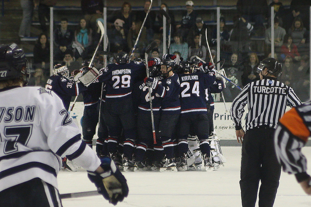 The UConn men's ice hockey team celebrates after sophomore forward Corey Ronan's overtime game winning goal against New Hampshire in Durham, New Hampshire on Saturday, Feb. 27, 2016. (Ian Bethune/The UConn Blog)