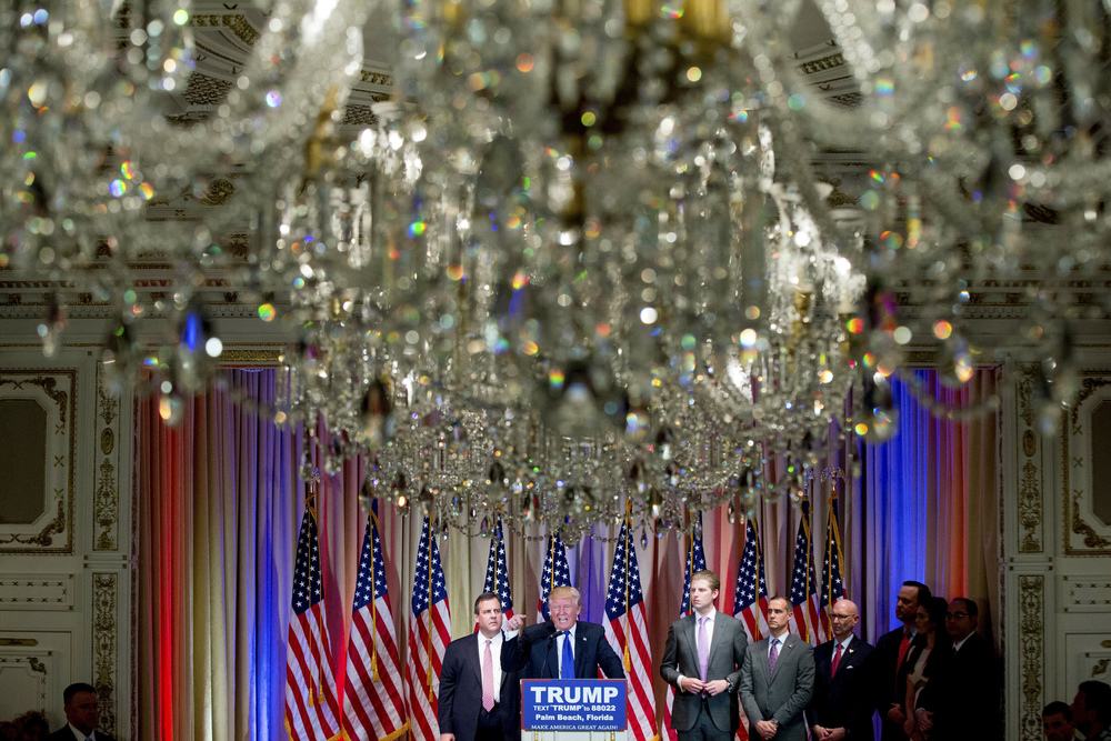 Republican presidential candidate Donald Trump, accompanied by New Jersey Gov. Chris Christie, left, and his son, Eric Trump, third from left, takes questions from members of the media during a news conference on Super Tuesday primary election night in the White and Gold Ballroom at The Mar-A-Lago Club in Palm Beach, Fla., Tuesday, March 1, 2016. (AP Photo/Andrew Harnik)