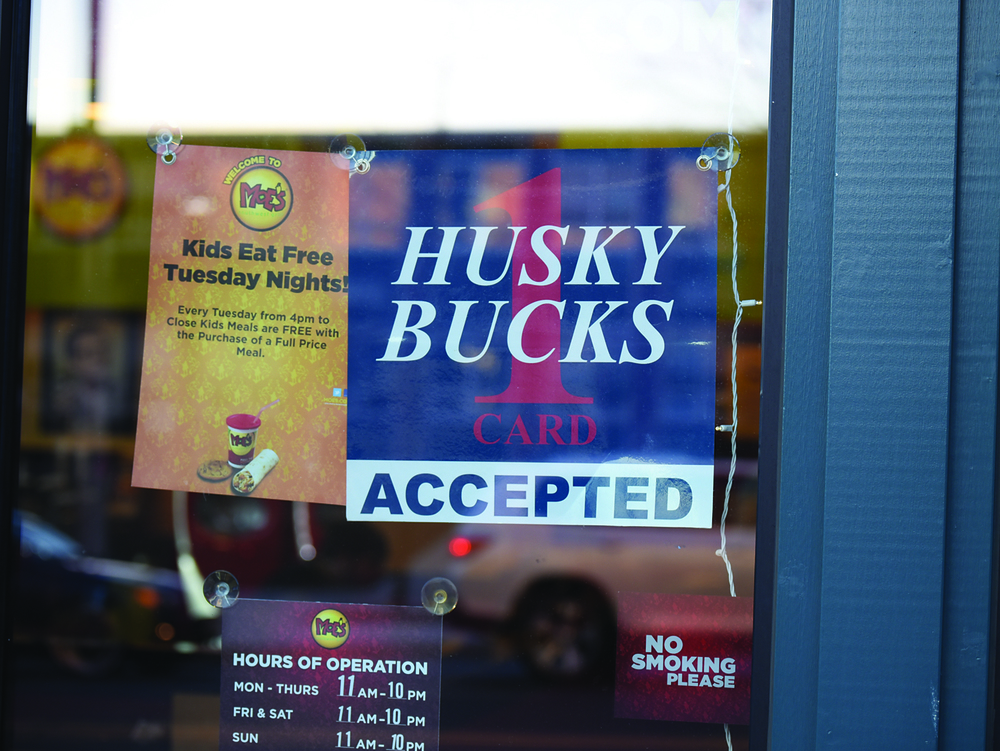 "A ""Husky Bucks Accepted"" sign hands in the doorway of Moe's in Storrs Center. Husky Bucks sales for this year are expected to pass last year's sales of more than $2.5 million. (Zhelun Lang/Daily Campus)"