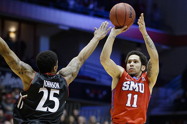 SMU's Nic Moore (11) shoots over Cincinnati's Kevin Johnson (25) during the second half of an NCAA college basketball game, Sunday, March 6, 2016, in Cincinnati. Cincinnati won 61-54. (AP Photo/John Minchillo)