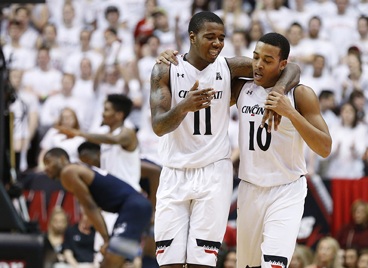 Cincinnati's Gary Clark (11) and Troy Caupain (10) encourage each other during the second half of an NCAA college basketball game against Connecticut, Saturday, Feb. 20, 2016, in Cincinnati. (AP Photo/Gary Landers)