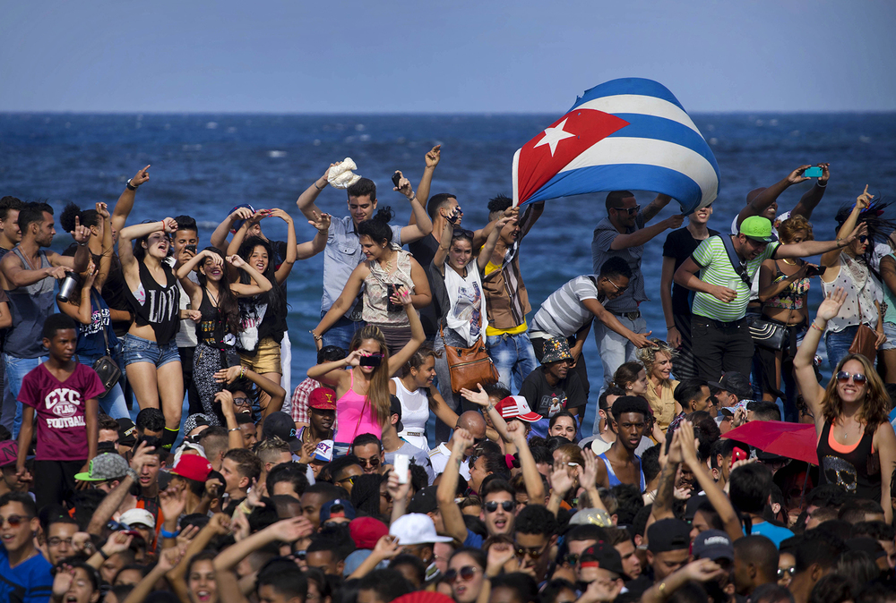 Fans dance on Havana's seafront during a free concert by the U.S. electronic music group Major Lazer in Havana, Cuba, Sunday, March 6, 2016. (AP Photo/Ramon Espinosa)