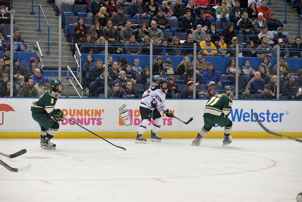 Karl El-Mir skates along the board during UConn's loss to Vermont at the XL Center. El-MIr scored two goals during the Huskies' series. (Amar Batra/The Daily Campus)