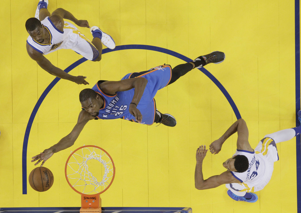 Oklahoma City Thunder's Kevin Durant (35) drives to the basket between Golden State Warriors' Harrison Barnes, left, and Shaun Livingston during the second half of an NBA basketball game Thursday, March 3, 2016, in Oakland, Calif. Golden State won 121-106. (AP Photo/Jeff Chiu)
