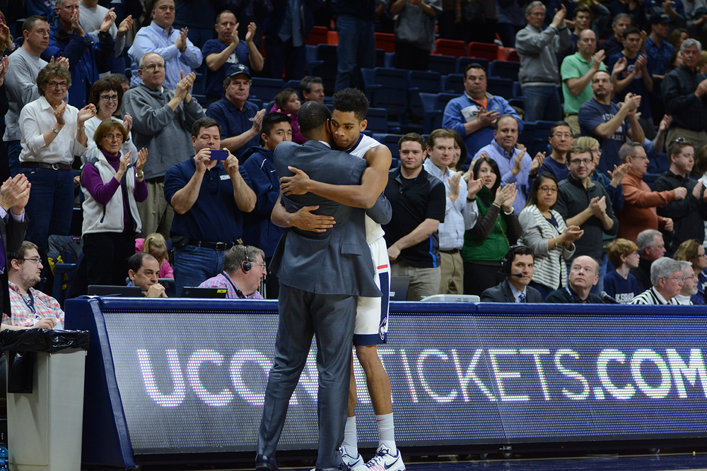 Kevin Ollie and Shonn Miller embrace on Senior Day at Gampel Pavilion. Ollie gave us the namesake of our new podcast, 384 Decision. He is quite fond of saying that he likes to make difficult choices while driving home on Route 384. (Matthew Zabierek/The Daily Campus)