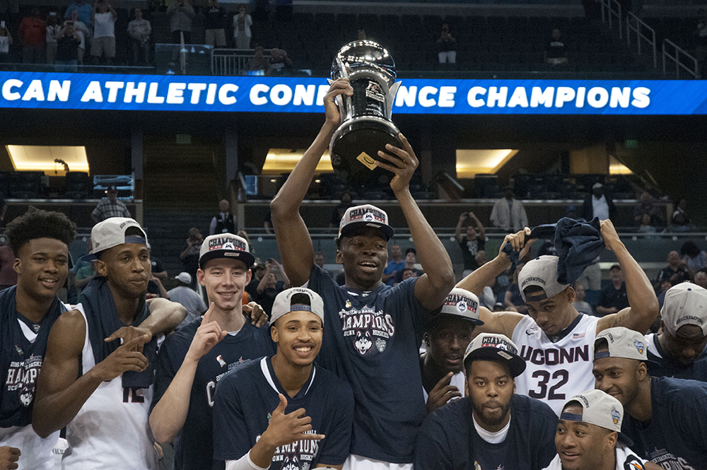 The UConn men's basketball team poses with the trophy after winning the American Athletic Conference Championship by defeating Memphis 72-58 at the Amway Center on Sunday March 13, 2016. It's UConn's first conference tournament championship since winning the Big East tournament in 2011. (Ashley Maher/The Daily Campus)