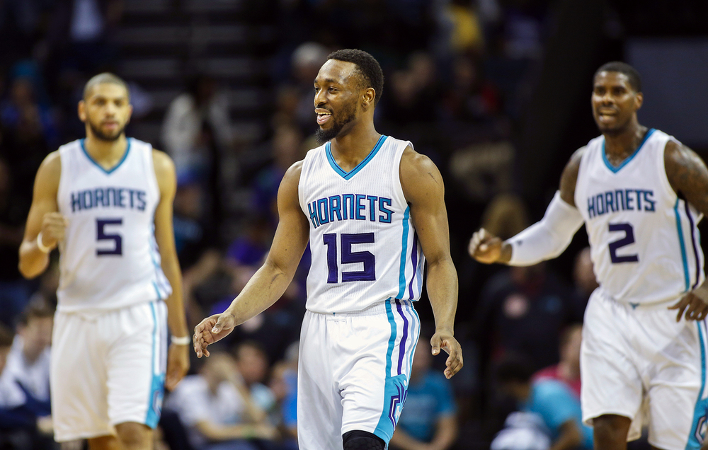 Charlotte Hornets guard Kemba Walker, center, smiles as teammates Nicolas Batum, left and Marvin Williams look on after Walker hit a 3-pointer in the closing seconds against the New Orleans Pelicans in the second half of an NBA basketball game in Charlotte, N.C., Wednesday, March 9, 2016. Charlotte won 122-113. (AP Photo/Nell Redmond)