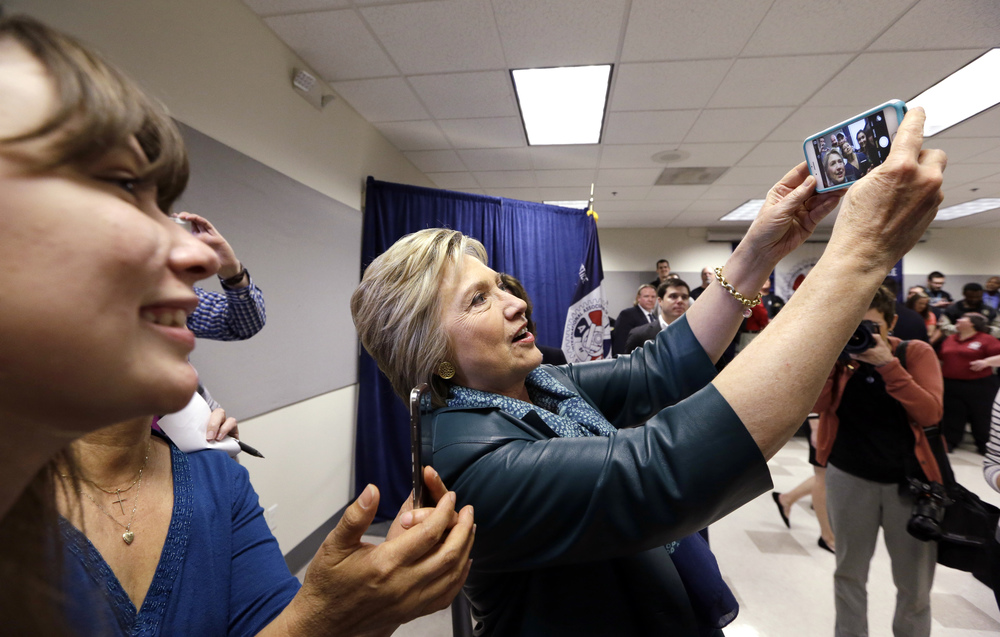Democratic presidential candidate Hillary Clinton takes a selfie photo for a supporter following a campaign event at the Boeing Machinists' union hall Tuesday, March 22, 2016, in Everett, Wash. (AP Photo/Elaine Thompson)
