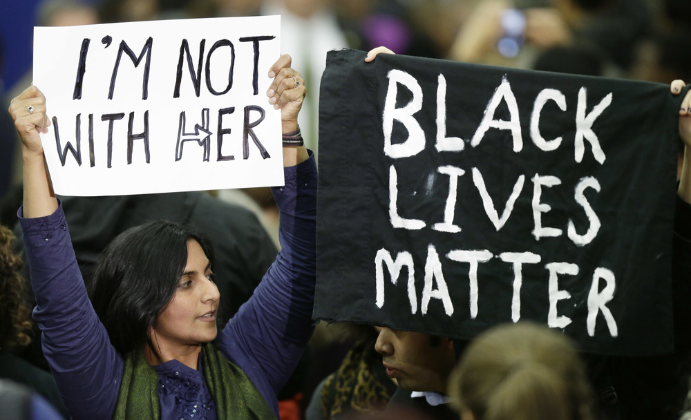 "Kshama Sawant, left, a member of the Seattle City Council, joins another protester in holding up a ""Black Lives Matter"" sign and a sign opposing Democratic presidential candidate Hillary Clinton, Tuesday, March 22, 2016, following a campaign rally at Rainier Beach High School in Seattle. (AP Photo/Ted S. Warren)"