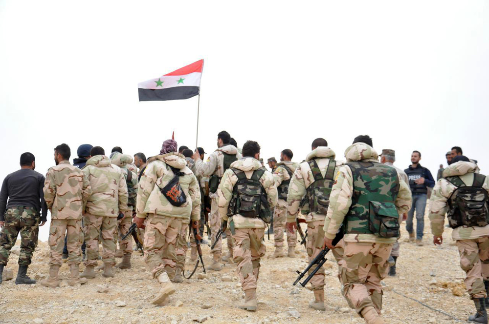 Syrian soldiers gather around a Syrian national flag in Palmyra, Syria, Sunday, March 27, 2016. Syrian state media and an opposition monitoring group say government forces backed by Russian airstrikes have driven Islamic State fighters from the historic central town of Palmyra, held by the extremists since May. (SANA via AP)