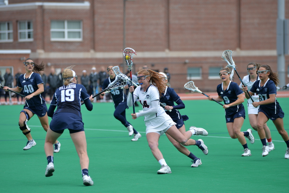 Freshman midfielder Brooke Jensen (14) cuts through Villanova defenders in a game at the George J. Sherman Family Sports Complex on Saturday, March 26. UConn defeated the Wildcats 13-8. (Amar Batra/The Daily Campus)