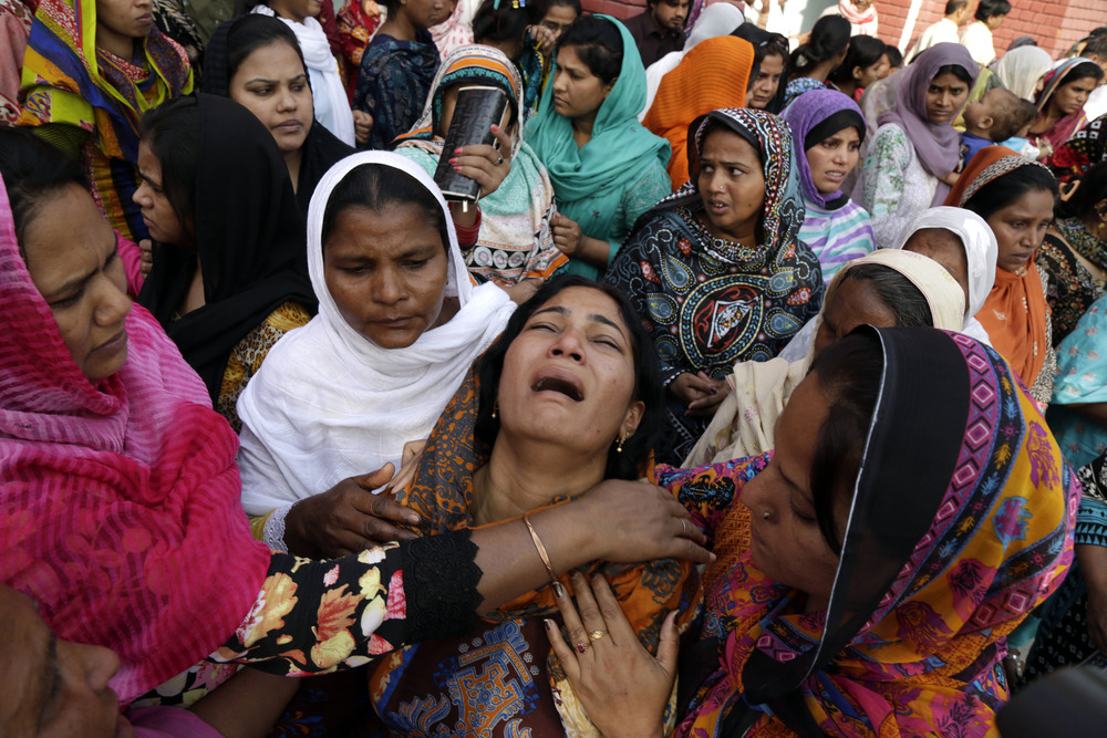 People try to comfort a Pakistani Christian mother during the funeral of her two daughters, killed in a suicide bombing Sunday, in Lahore, Pakistan, Thursday, March 30, 2016. The massive suicide bombing by a breakaway Taliban faction targeted Christians gathered for Easter Sunday in a park in Lahore, killing at least 70 people, mostly Muslims. (AP Photo/K.M. Chaudary)