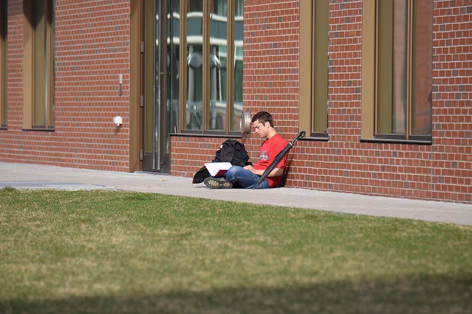 A student catches up on some reading on a beautiful day at UConn. (Zhelun Lang/The Daily Campus)